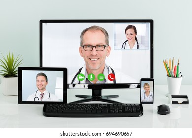 Male and female doctors having conference call on various technologies at hospital