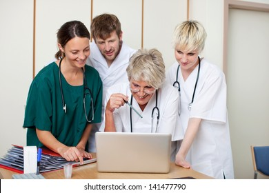 Male and female doctors looking at laptop in hospital