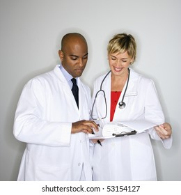 Male and female doctors reading paperwork.