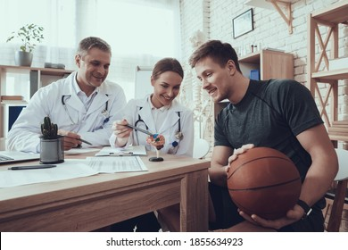 Male and female doctors in white gowns with stethoscopes in office with basketball player. Young basketball player sitting at the doctor appointment in the office.