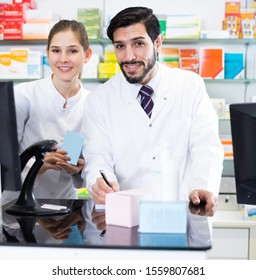 Male and female druggists are attentive stocktaking drugs with note near computer in pharmacy.