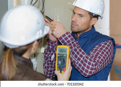 male and female electricians testing circuit with multimeter