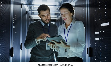 Male and Female IT Engineers in Data Center / Server Room, They are Talking. One of them Holds Tablet Computer.