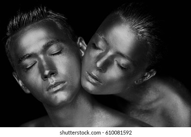 Male and female face around. The woman's head lies on the shoulder of a man. All painted in gold paint, the feeling of a single whole organism. Black and white