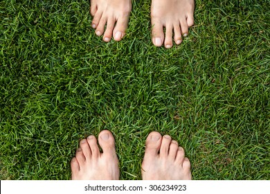 Male and female feet over green grass