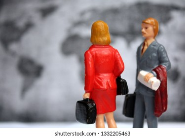 Male and female figure little people and defocused earth map in background