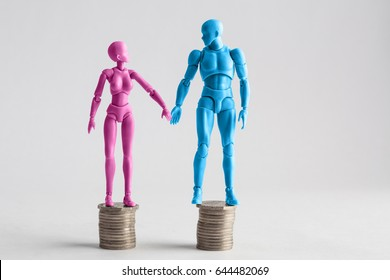 Male and female figurines holding hands looking at each other, standing on top of equal piles of coins. Income equality concept with copy space