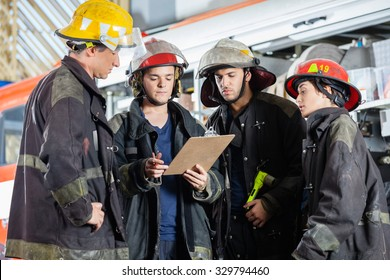 Male and female firefighters reading clipboard together at fire station