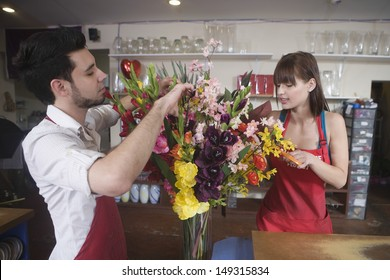 Male and female florists working together in flower shop