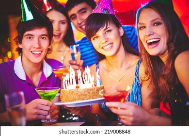 Male and female friends holding cake with burning candles and drinks on birthday party