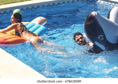 Male and female friends with inflatable fish and airbed having fun in pool together.