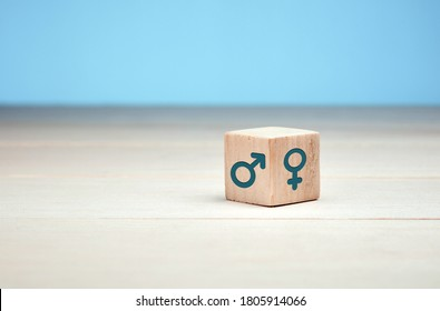 Male and female gender icons or symbols on two sides of a wooden cube. Gender equality concept.