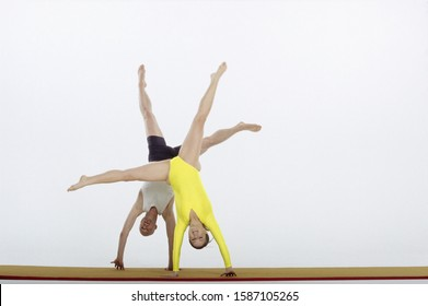 Male and female gymnasts cartwheeling together