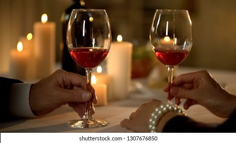 Male and female hand holding glasses with red wine on table, romantic tradition