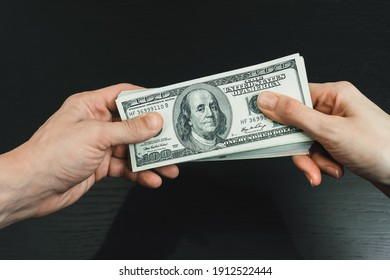 Male and female hand holding a wad of dollars on a black background close-up. Concept of bribery, assistance, and remuneration