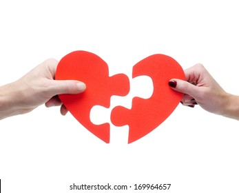 Male and female hand matching red jigsaw heart halves over white background