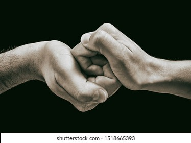 Male and female hands connect with each other. Isolated on black. Image.