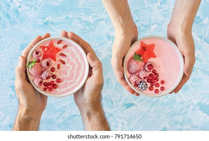 Male and Female Hands Each Holding a Pink Berry Yogurt Smoothie Bowl Topped with Chilled and Fresh Fruit