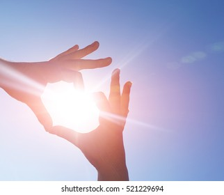 Male and female hands in the form of love heart - Silhouette hands in shape of heart with sun in the middle of the heart and sky in the backgroud