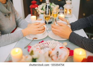 male and female hands hold cups of tea (romantic evening)