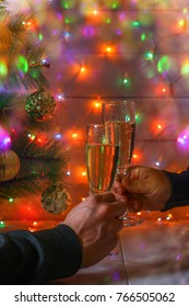 Male and female hands hold a glass of champagne against the backdrop of the New Year tree and garlands