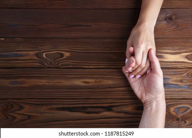 Male and female hands holding each other on dark wooden table