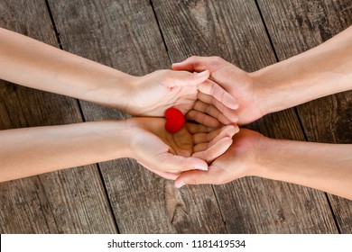 male and female hands holding red heart on wooden background.