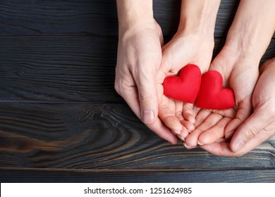 Male and female hands holding two red love hearts on wooden background, view from above