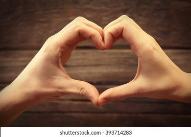 Male and female hands making heart with fingers on wooden background