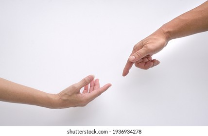 Male and female hands reaching out to each other, creation of adam sign. Isolated on white background. Concept of connection and human relations.