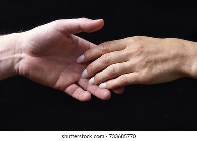 Male and female hands together on black background