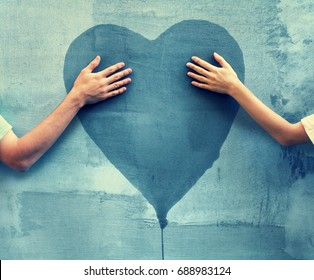 Male and female hands touching painted heart on concrete wall