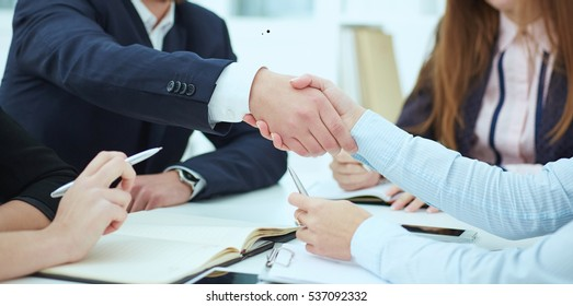 Male and female handshake in office. Serious business and partnership concept. Partners made deal, sealed with handclasp.