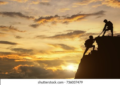 Male and female hikers climbing up mountain cliff and one of them giving helping hand. People helping and, team work concept.