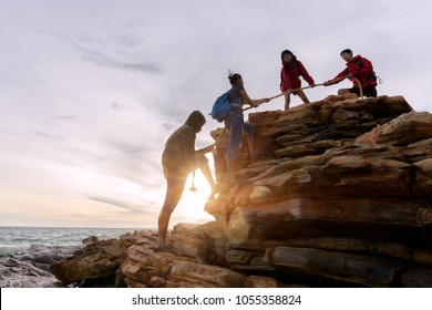 Male and female hikers climbing up silhouette mountain cliff . helps and team work concept.