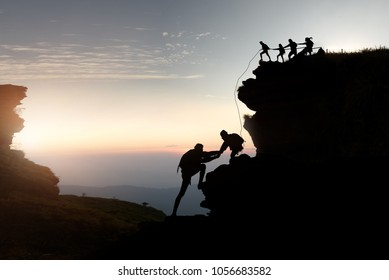 Male and female hikers climbing up silhouette mountain cliff . teamwork ,success ,helps , business concept.