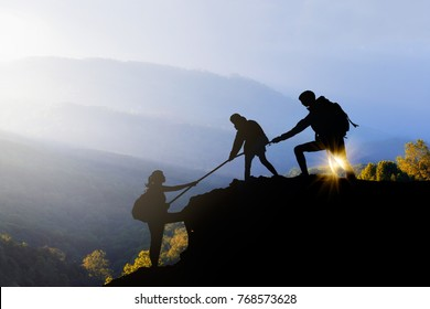 Male and female hikers climbing up silhouette mountain cliff and one of them giving helping hand.helps and, team work concept.