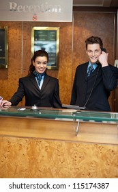 Male and female at hotel reception busy working. Man attending phone call