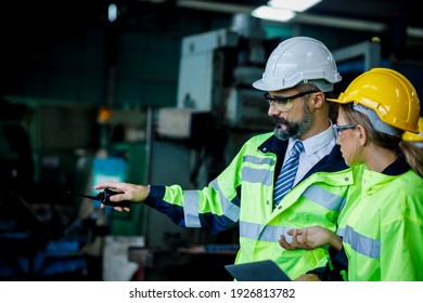 Male and female industrial engineer explaining the workplace. He is holding the walkie talkie on his hand while the pointing.