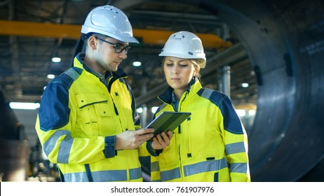 Male and Female Industrial Engineers in Hard Hats Discuss New Project while Using Tablet Computer. They're Making Calculated Engineering Decisions.They Work at the Heavy Industry Manufacturing Factory