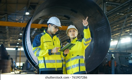 Male and Female Industrial Engineers Have Discussion while Using Tablet Computer. They Work in a Heavy Industry Manufacturing Factory.