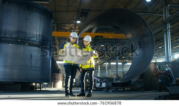 Ingenieure von männlichen und weiblichen Industriebetrieben betrachten Projektkonzepte, während sie in der Mitte der Fabrik für die Herstellung von energiegeladenen Schwerindustrien durch Rohrleitungen umrahmen