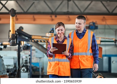 Male and Female Industrial worker use tablet and Walking Through Heavy Industry Manufacturing Factory. They Wear Hard Hats and Safety Jackets