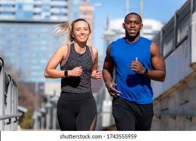 Male and female joggers running through urban city background, smiling, happy healthy lifestyle, african american and caucasian woman