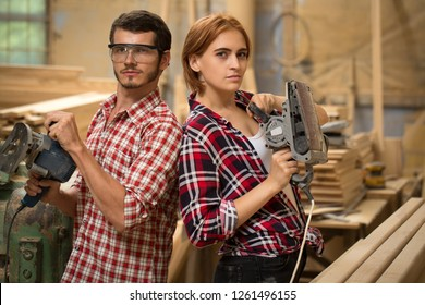 Male and female joiners holding grinding machines for machining wood. Handsome bearded man in safety glasses and beautiful woman with ginger hair looking at camera and posing.