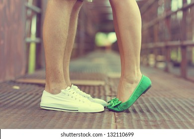 Male and female legs and green shoes