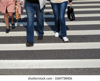 Male and female legs on the pedestrian Zebra lines. A group of people crossing the road. Pedestrian safety concept