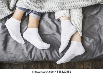 male and female legs in socks under a blanket in a bed