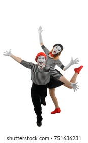 Male and female mimes dancing with wide open arms. Spectacular pantomime show performed by mime artists, dressed in striped shirts, bow ties and berets.