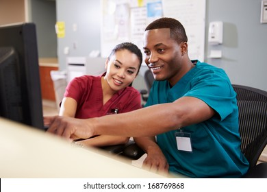 Male And Female Nurse Working At Nurses Station